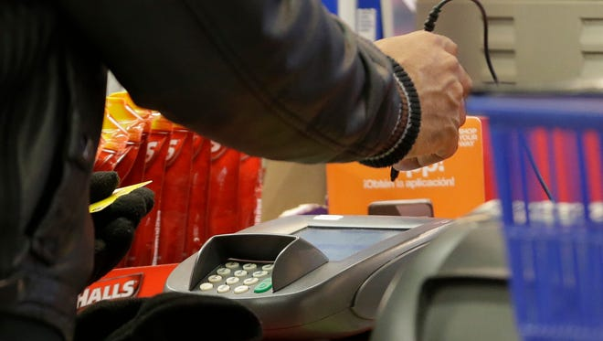 A man pays with a credit card while shopping at Kmart.