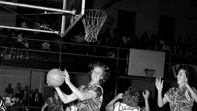 Nera White, left, of the Nashville Business College boldly lays claim to the basketball and she has no challengers at this point against Iowa Wesleyan at Litton High SchoolÕs gym Dec. 16, 1963. With back to White is Peg Peterson (22) of Wesleyan and watching in awe is Nera's teammate, Mary Garber (45).