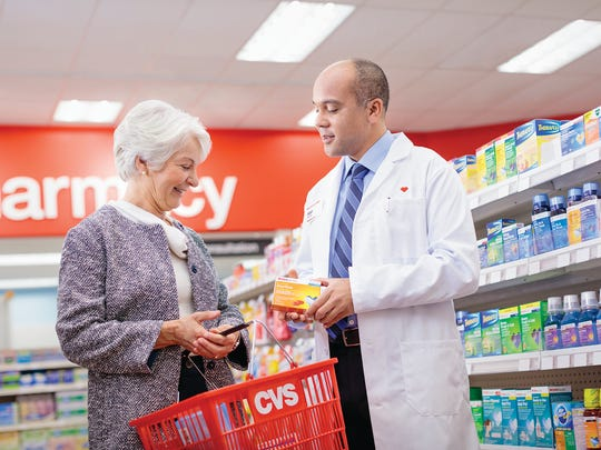 A CVS pharmacist aiding a senior woman with a product-buying decision.