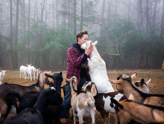 Dairy goat farm hand, Sandra Coffman, kisses a Saanen