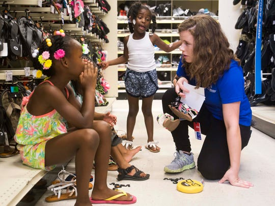 At center Boys & Girls Clubs of the Tennessee Valley kid Ava Burdine 5, talks to Academy Sports & Outdoors employee Josie O'Gorman as she picks out sandals with friends in West Knoxville Wednesday, July 26, 2017. 30 boys & girls from the club got to each go on a $100 shopping spree for back to school items at the store.