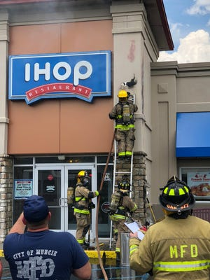 Firefighters battle a blaze at the Muncie IHOP the afternoon of Monday, May 28, 2018 after a cigarette butt tossed into mulch caught fire. Damage appeared to be limited to the facade and lobby area.