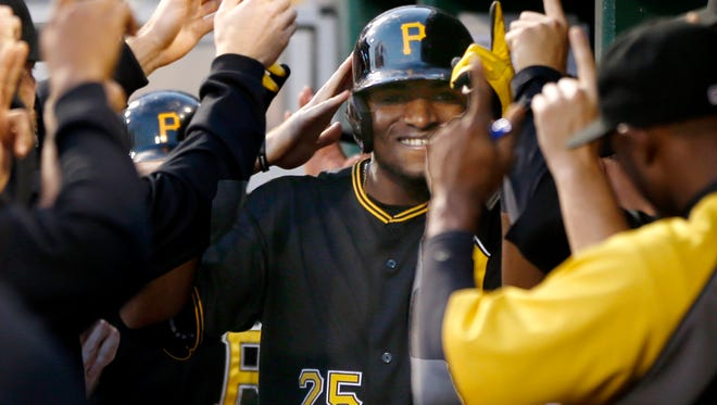 Pittsburgh Pirates' Gregory Polanco (25) is greeted by teammates in the dugout after hitting a three-run home run against the New York Mets.
