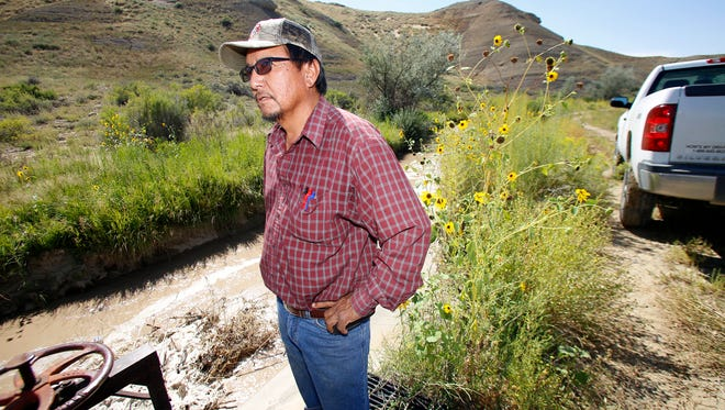 Shiprock irrigation supervisor Marlin Saggboy watches water flow past an irrigation gate Aug. 28, 2015, along the Fruitland Irrigation canal in Upper Fruitland, several weeks after the Gold King Mine spill caused toxic waste water to flow into the Animas and San Juan rivers.