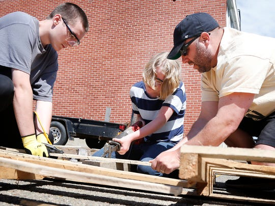 Corning-Painted Post High School junior Kristen Crooker saws through planks Wednesday while junior Seth Buchanan, left, and teacher Kevin Scanlon steady the pallet. High school students are building community garden beds behind South Corning Town Hall.