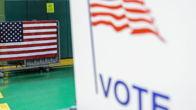 A poll worker looks over the directions for starting up the vote tabulator as workers get ready for the day before polls open at Ward 2, Precinct 16 at Parker Baptist Church  Tuesday, Nov. 8, 2016 in Lansing.