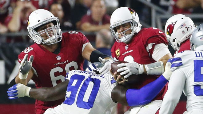 Arizona Cardinals quarterback Carson Palmer (3) gets sacked by Dallas Cowboys defensive end Demarcus Lawrence (90) during the second quarter of Monday Night Football at University of Phoenix Stadium in Glendale, Ariz. September 25, 2017.