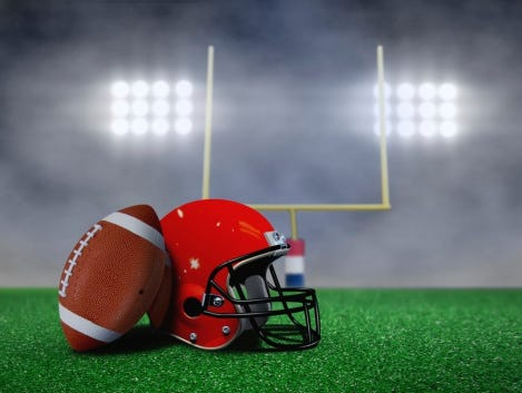 Football and Helmet on Field with Goal Post under Spotlights