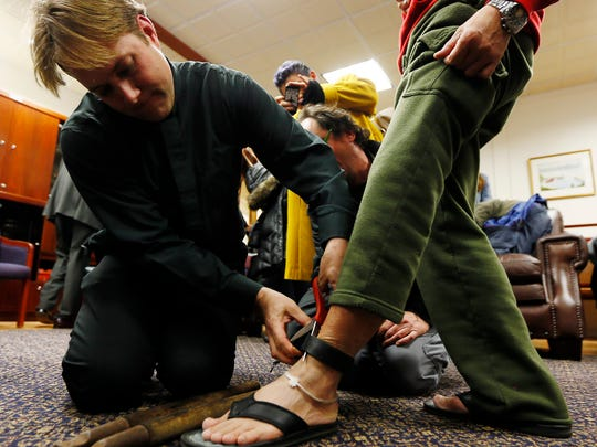 Rev. Seth Kaper-Dale of the Highland Park Reformed Church cuts off a Homeland Security ankle bracelet from Yohanes Tasik as two other Indonesian men were detained today, another claiming sanctuary at the church. January 25, 2018. Highland Park, NJ.