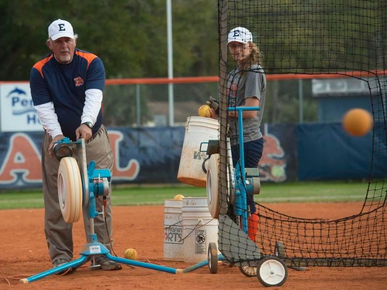 Escambia High School softball coach, Glenn Bousquet, left, get help from player, Sarah Crutchfield, right, setting up for hitting practice in preparation for Thursday night's District 1-7A game against Tate.