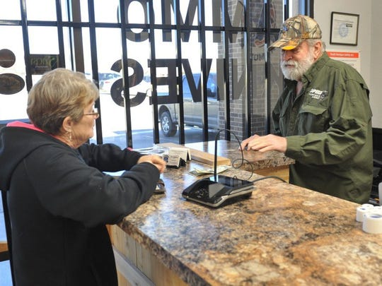 Texoma Armory owner Gary Barlow (right) chats with customer Kathy Richarson during the store's grand-reopening event on Feb. 5, 2016.