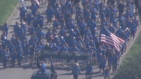 Community members march in memory of Deputy Darren Goforth.