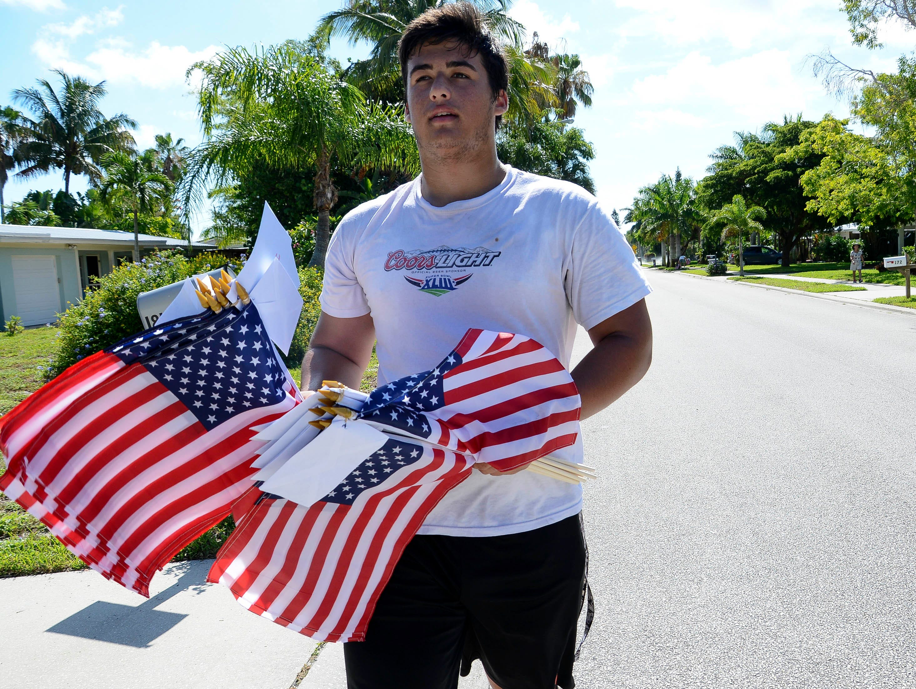 Alex Iervasi helps set out American flags Thursday morning in Satellite Beach. Students from Satellite High's football and ROTC squads help distribute American flags as part of a fundraiser for the school.