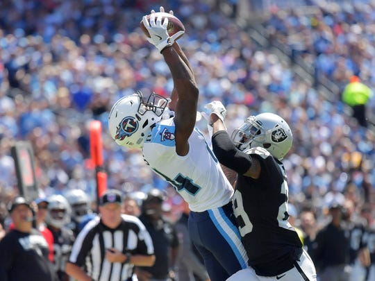 Tennessee Titans wide receiver Corey Davis (84) catches a pass against Oakland Raiders cornerback David Amerson (29) during the first half at Nissan Stadium.