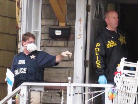 U.S. Secret Service agents step outside a house at