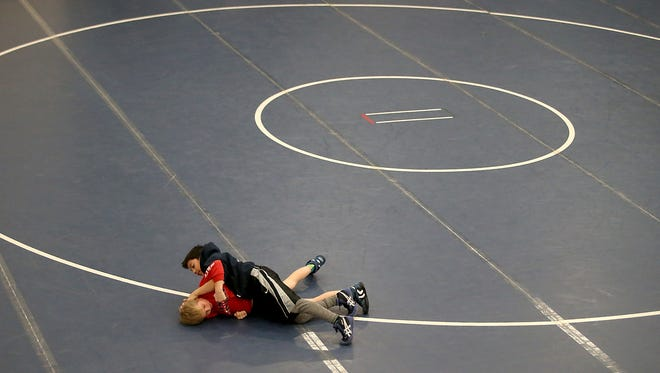 Youngsters grapple on the mat in between rounds during the Olympic Duals Wrestling Tournament at the Kitsap sun Pavilion on Saturday, Dec. 10, 2016. (MEEGAN M. REID / KITSAP SUN)