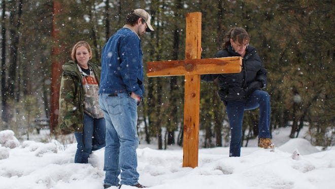 "Mourners stand near a wooden cross on Highway 395 near Burns, Ore., on Jan. 29, 2016, at the location where Robert ""LaVoy"" Finicum was shot dead and others were arrested by the FBI in connection with the occupation of a federal refuge."