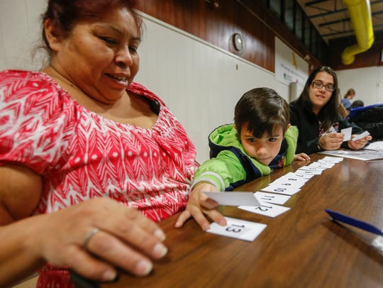 Kade Betts, 5, works on numbers with his mom Kayla