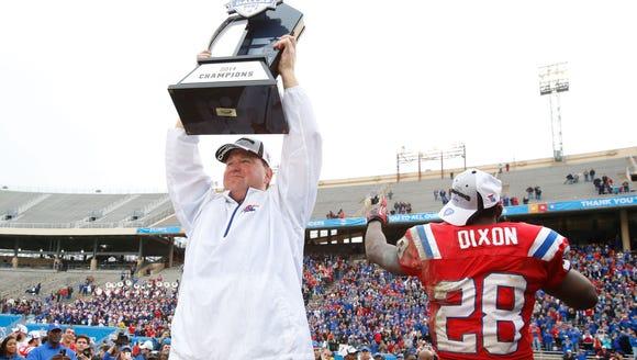 Louisiana Tech coach Skip Holtz holds up the trophy