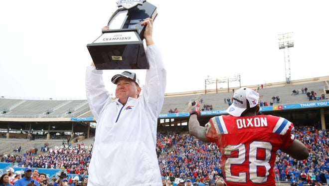 Louisiana Tech coach Skip Holtz holds up the trophy after the Bulldogs' Heart of Dallas Bowl win against Illinois last December.