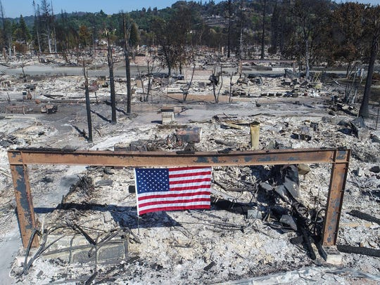 An American flag flies over the remnants of a house