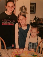 Stephanie Dickrell, 13, Emily Whipple, 9, and Erin Drees, 6 pose for the obligatory birthday photo near their shared cake near Plymouth, Wis. in 1999.