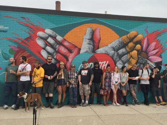 Nearly 20 participating local artists in the upcoming Murals in the Market festival stand in front of a just-painted work by the Los Angeles-based artist called Meggs (seventh from the right) in Eastern Market.