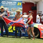 Race fans make a photo with a Confederate flag in the Fan Zone before a NASCAR Sprint Cup series auto race at Daytona International Speedway, Sunday, July 5, 2015, in Daytona Beach, Fla. (AP Photo/Terry Renna)
