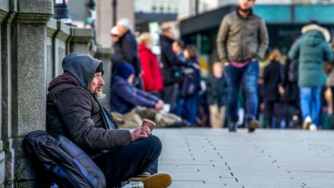 A man walks past a begging man in downtown Hamburg, Germany, on Nov. 17, 2017.