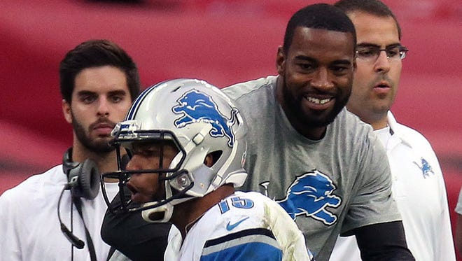 Calvin Johnson watches as Golden Tate completes a reception Sunday.