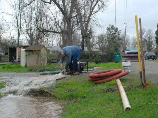 Joe Lilienthal of PJ Construction, pumps water from a clogged culvert on Hermosa Road in Shasta County.