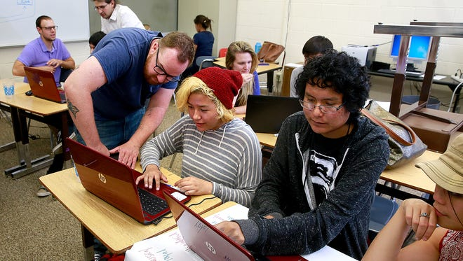 Charles Sandidge, left, of Cultivating Coders leads an eight-week coding workshop on Thursday at Shiprock High School as students Courtney Elwood, Rius Goodman and Kristin Macapagal listen.