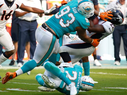 FILE - In this Dec. 3, 2017, file photo, Miami Dolphins defensive tackle Ndamukong Suh (93) and Miami Dolphins strong safety T.J. McDonald (22), tackle Denver Broncos running back C.J. Anderson (22), during the first half of an NFL football game, in Miami Gardens, Fla. The Miami Dolphins appear ready to move on without their defensive anchor. Miami is discussing releasing five-time Pro Bowl tackle Ndamukong Suh when the NFL's new year begins Wednesday, a person familiar with the situation said Monday, March 12, 2018. The person said nothing has been finalized, and confirmed the conversations to The Associated Press on condition of anonymity because the Dolphins have not commented.(AP Photo/Wilfredo Lee, File)