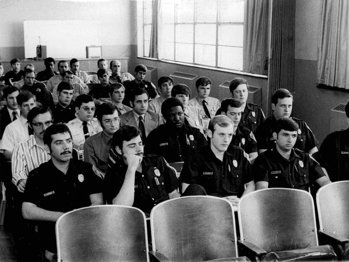 Rookies listen to lecture at police academy. (Staff