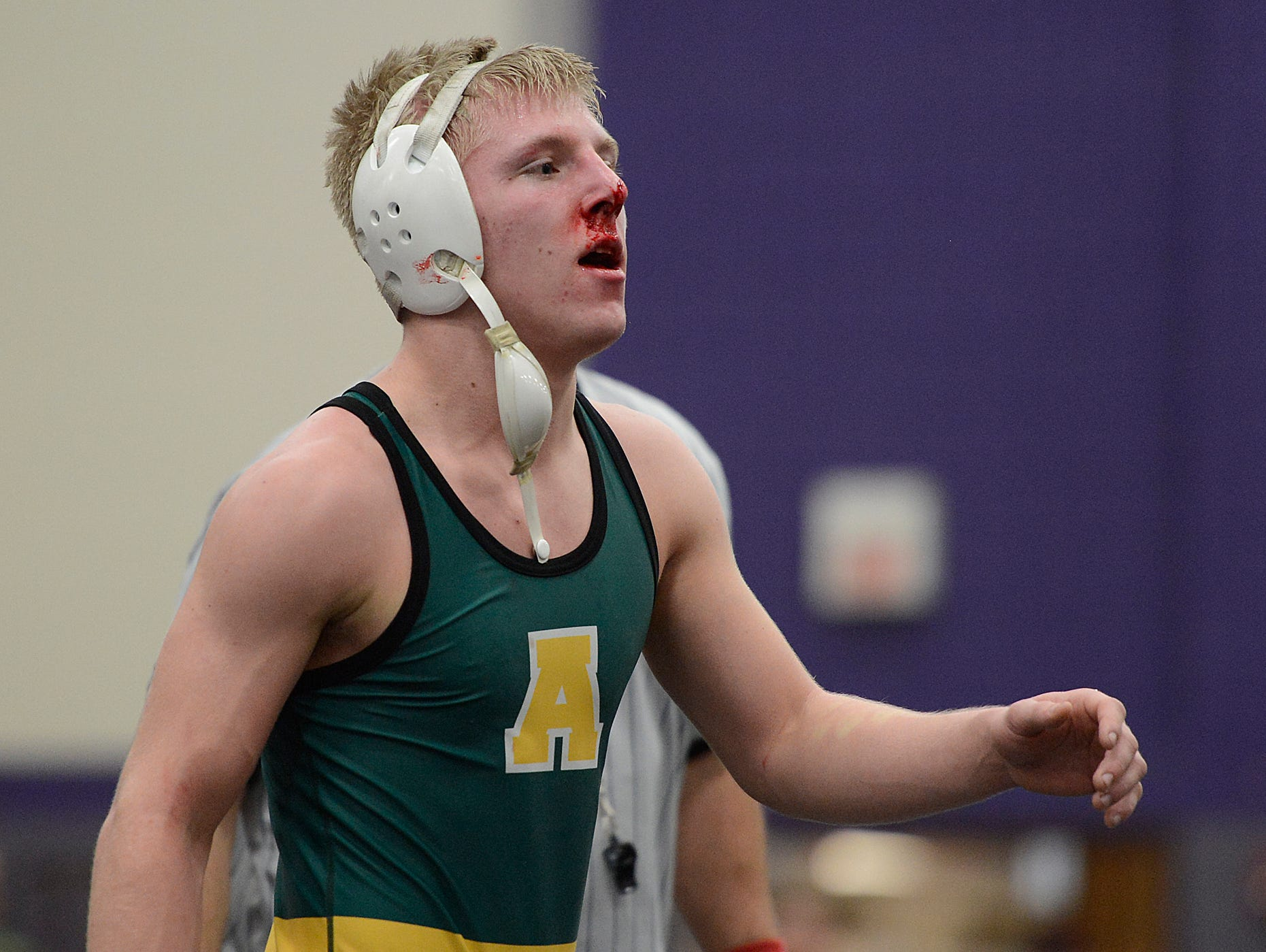 Ashwaubenon's Zac Benton walks off the mat with a bloody nose after defeating Pulaski's Jake Gille in the 138-pound championship match during Saturday's WIAA Division 1 wrestling sectionals at Green Bay West High School.