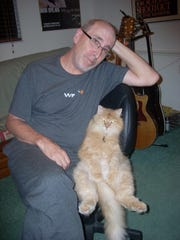 John Rinkenbaugh relaxes with his cat, Rudy.