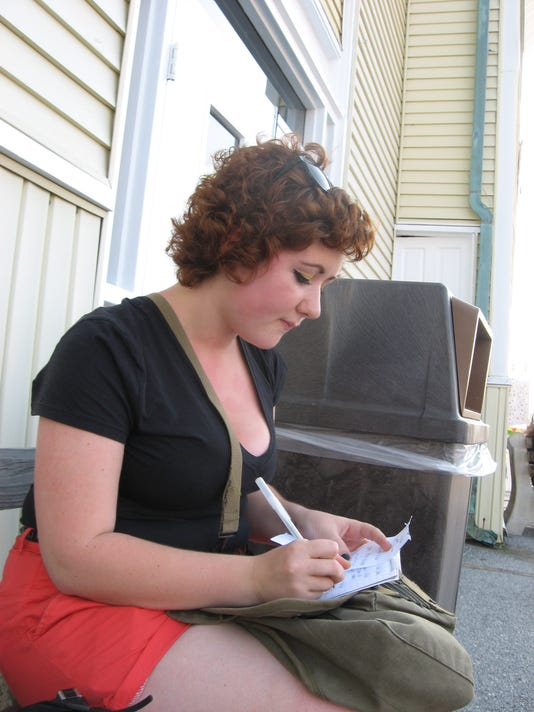 Spring Grove Area High School senior Bria Topper copies notes in front of the Old Main building at the York Fair on Students' Day, Tuesday, Sept. 12.