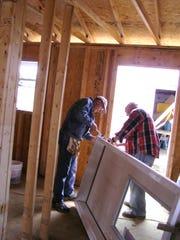 John Luetzelschwab and Ron Burge work on a door frame.