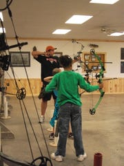 Leaders help to guide young 4-H members during a shooting sports activity.