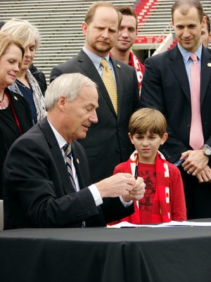 Murphy Wardlaw watches as Gov. Asa Hutchinson signs a bill on the field at War Memorial Stadium on Wednesday, Feb. 22, 2017, in Little Rock placing the stadium under the control of the state Parks and Tourism Department.