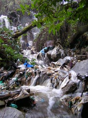 Water cascades over a towering trash pile in Gorst