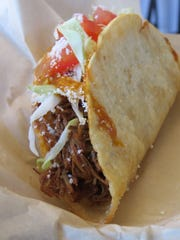 A hard-shell taco with barbacoa (shredded beef) filling