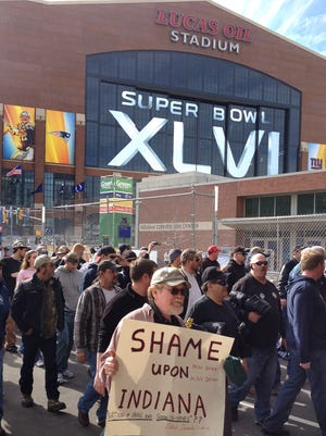 """Thousands of union workers march past the Indiana Convention Center and Lucas Oil Stadium on Feb. 1, 2012, days before Super Bowl XLVI, to protest the state's """"right to work"""" legislation."""