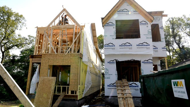 "Construction crews work on a pair of homes in East Nashville. Two ""tall skinny"" homes can be built on one lot when they are 6 feet apart, among other conditions."
