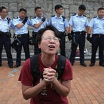 Student protesters raise their hands to show non-violent intentions as they resist police on Thursday, Oct. 2, 2014 in Hong Kong. They backed down after being reassured they could reoccupy the pavement outside the government compound's gate. Hong Kong police warned of serious consequences if pro-democracy protesters try to occupy government buildings, as they have threatened to do if the territory's leader doesn't resign.