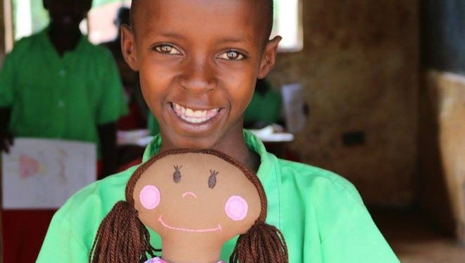 A girl at a school in Kenya smiles with a Whimsy doll given to her after Heart of Whimsy spoke to hundreds of girls at different schools throughout the country about self worth.