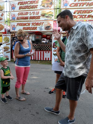 """""""Carnival Eats"""" host Noah Cappe, right, talks with GIbson Burkhardt, left, and Kailee Ward while filming a segment for The Cooking Channel show Friday, June 24, 2016 at the Wayne County 4-H Fair in Richmond."""