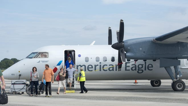 Passengers get off a Piedmont Airlines turboprop, flying under American Airlines' American Eagle banner, at the Salisbury-Ocean City: Wicomico Regional Airport.