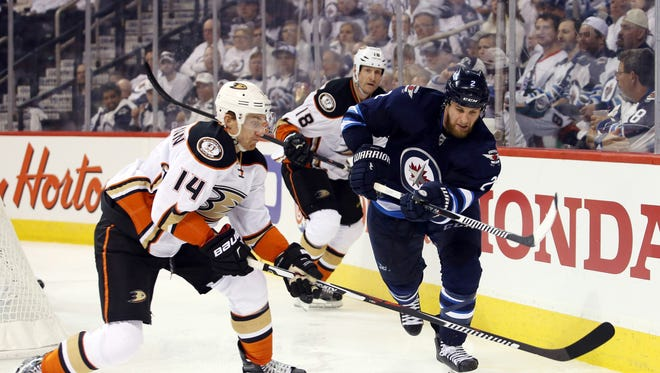 Anaheim Ducks left wing Tomas Fleischmann (14) looks to control the puck against Winnipeg Jets defenseman Adam Pardy (2) during third period in game three of the first round of the 2015 Stanley Cup Playoffs at MTS Centre.