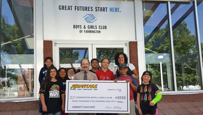 At center, Steve Melloy with Advantage Dodge poses with a check for $4,550 that the dealership recently presented to the Boys and Girls Club of Farmington. The dealership donated a portion of the proceeds from its Community Sales Event to the Farmington nonprofit.